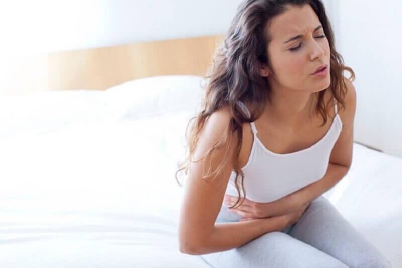 Kvinde med mavesmerter - aarsager til rygsmerter
