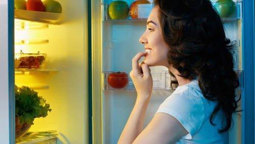 Kvinde kigger i køleskabet