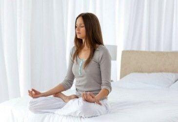 Kvinde der sidder ned og mediterer