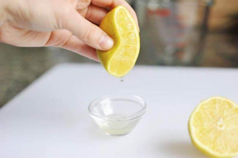 Hånd der presser citronsaft ud i en skål