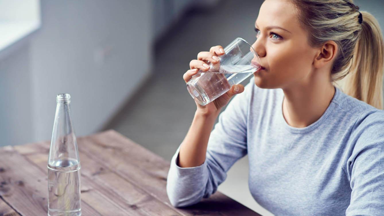 Blond kvinde der drikker vand