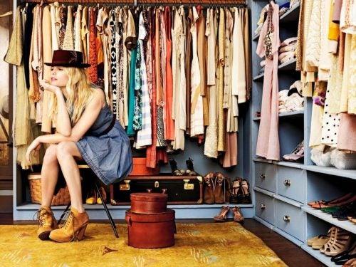 Kvinde der sidder og spekulerer ved sin garderobe