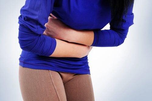 Kvinde står forover bøjet og holder sig for maveregionen pga mavepine