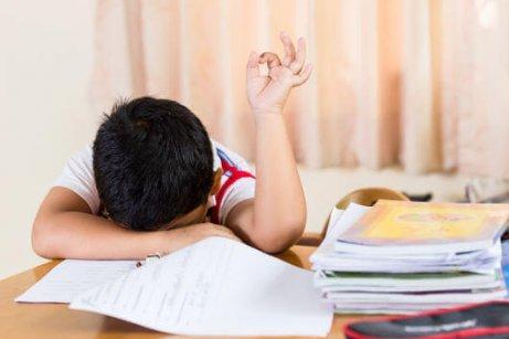 Søvnigt barn, der kæmper med lektierne.