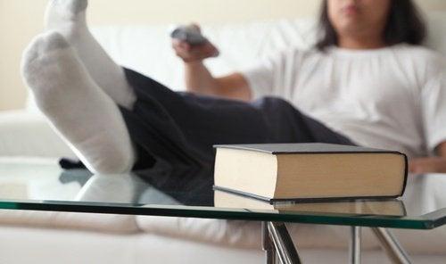 Stor bog paa et bord og person der sidder i en sofa - aelder dig hurtigere
