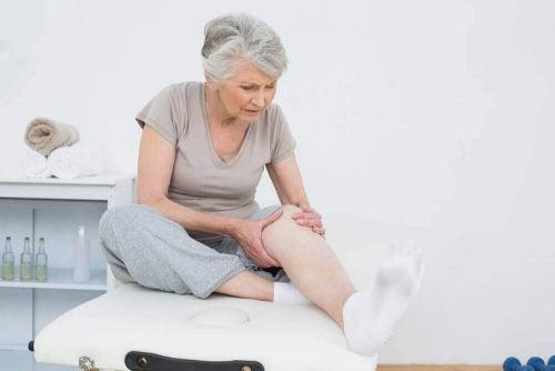 Aeldre kvinde tager sig til benet