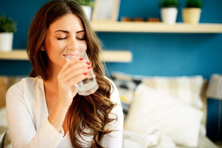 Kvinde drikker vand af glas - symptomerne paa mavekatar