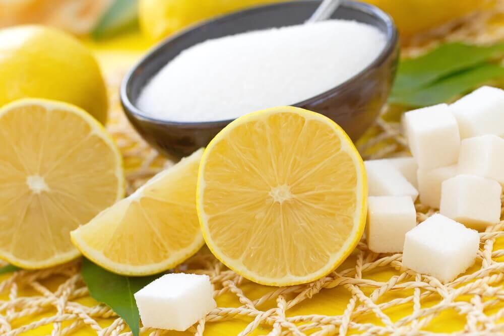 Friske citroner ved siden af sukkerskål.