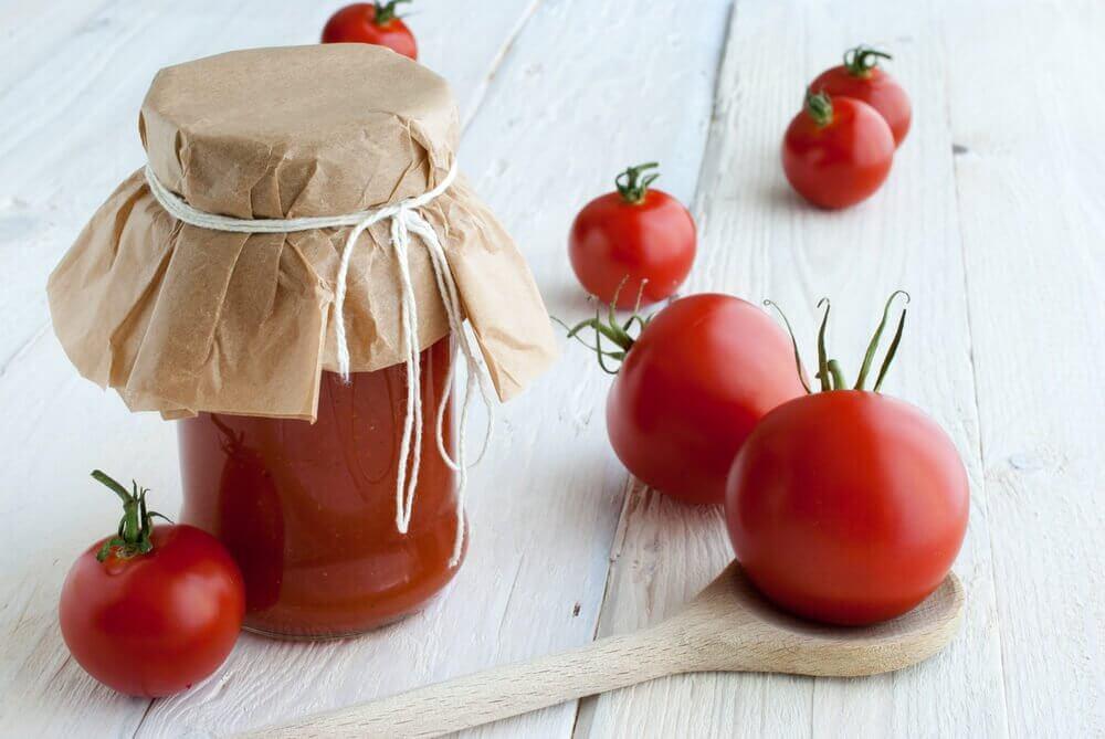 Glaskrukke med tomatsovs ved siden af friske tomater.