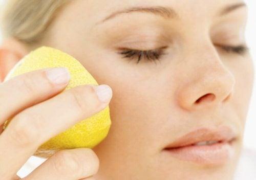 Kvinde der smoerer citron paa kinden - citron som naturlig kosmetik