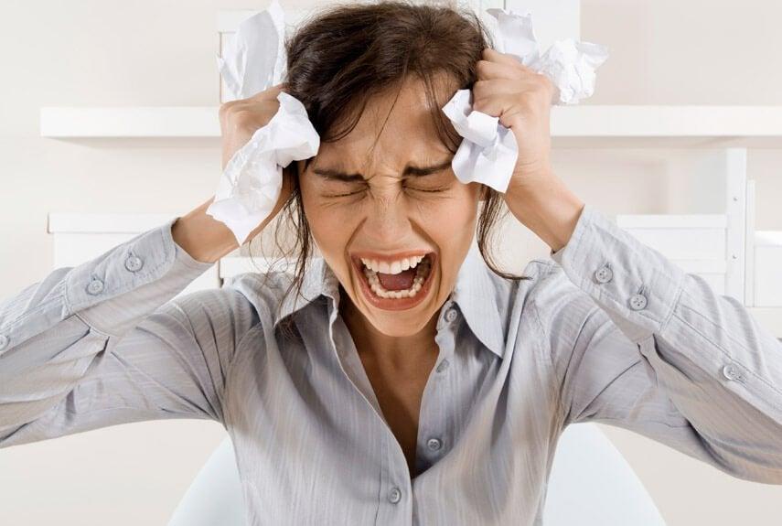 Kvinde holder sig til hovedet og skriger