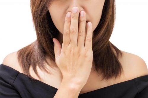 Kvinde der holder sig for munden