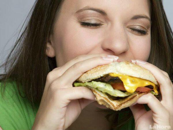 Kvinde spiser burger