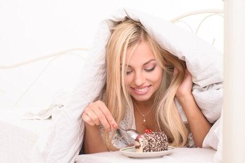 Kvinde der spiser kage under dynen