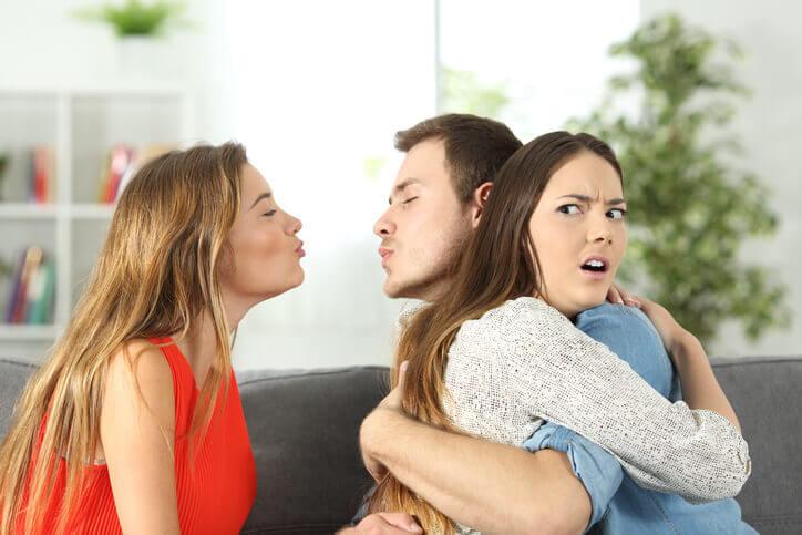 En mand krammer en kvinde, mens han proever at kysse en anden kvinde bag hendes ryg