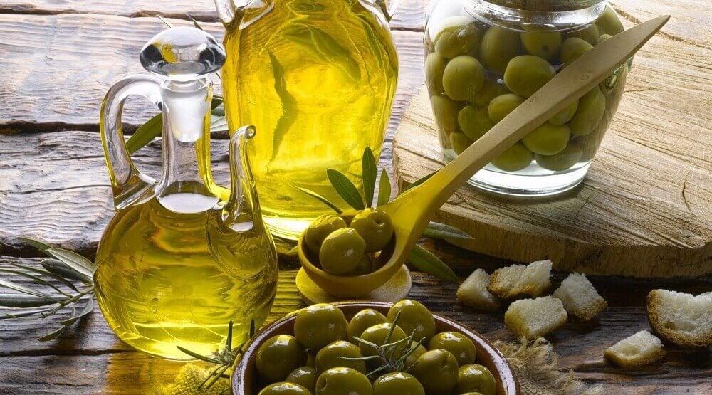 En skål oliven ved siden af en flaske olivenolie.