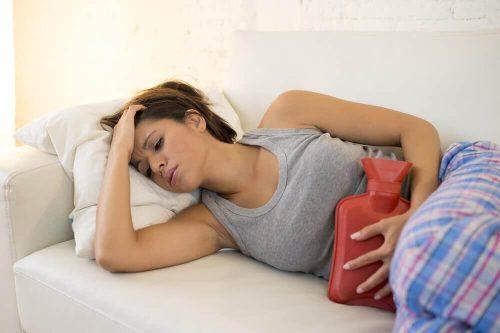En kvinde der ligger med varmepude for maven