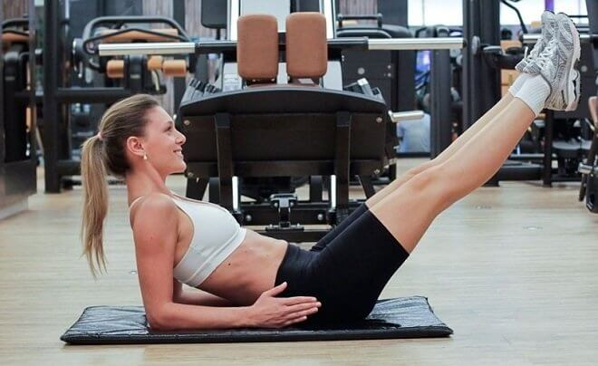Kvinde i fitnesscentret - tonede mavemuskler