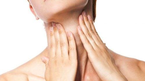 Kvinde der har sine haender paa sin hals