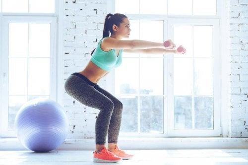 Kvinde der squatter med haandvaegte - flotte hofter