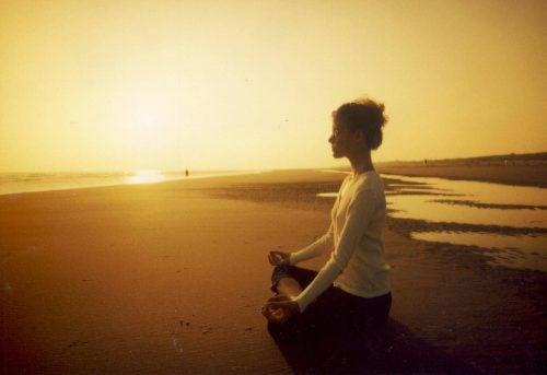 Kvinde der mediterer paa en strand
