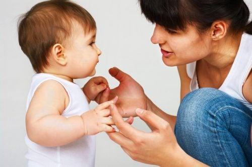 Mor sidder på hug og kigger sin baby i oejnene