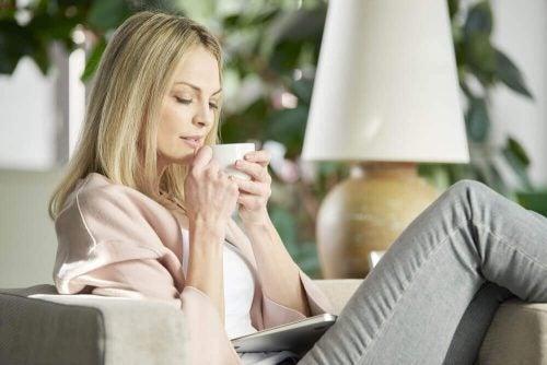 Kvinde der sidder og drikker te