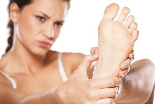 Kvinde holder sin fod.