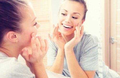 Kvinde smiler til sig selv i spejlet.