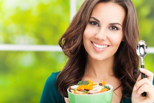 Kvinde spiser salat.