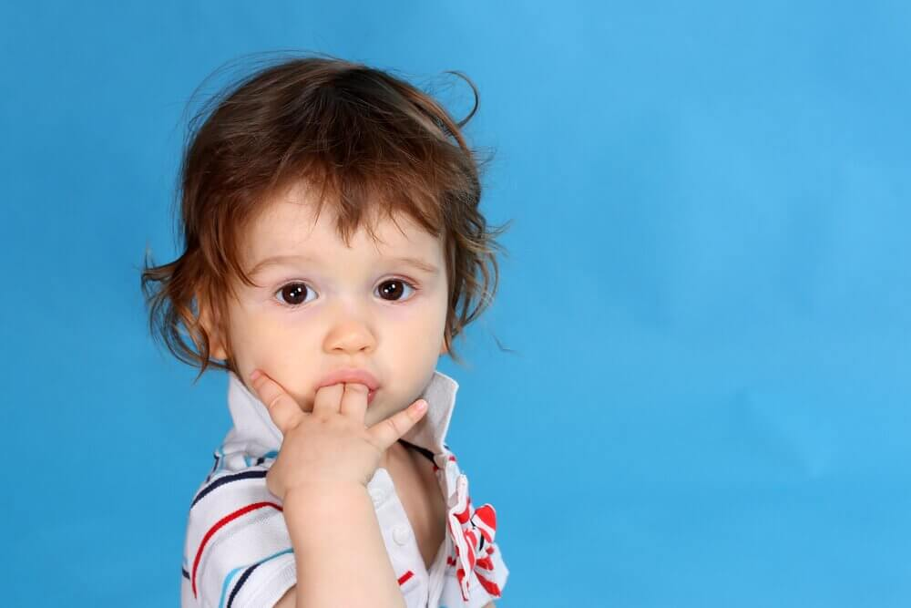 Lille barn med finger i mund.