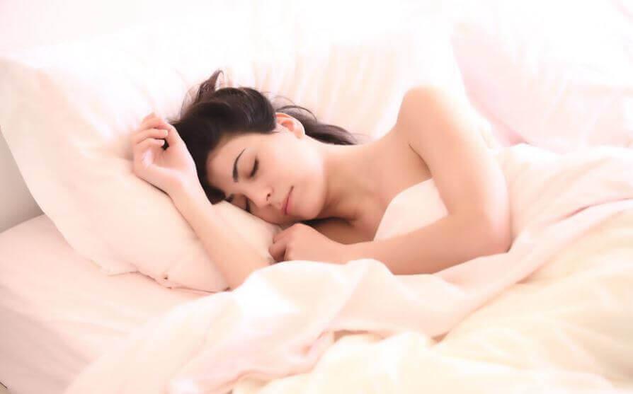 Kvinde sover i seng.