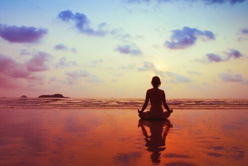 Kvinde mediterer på stranden