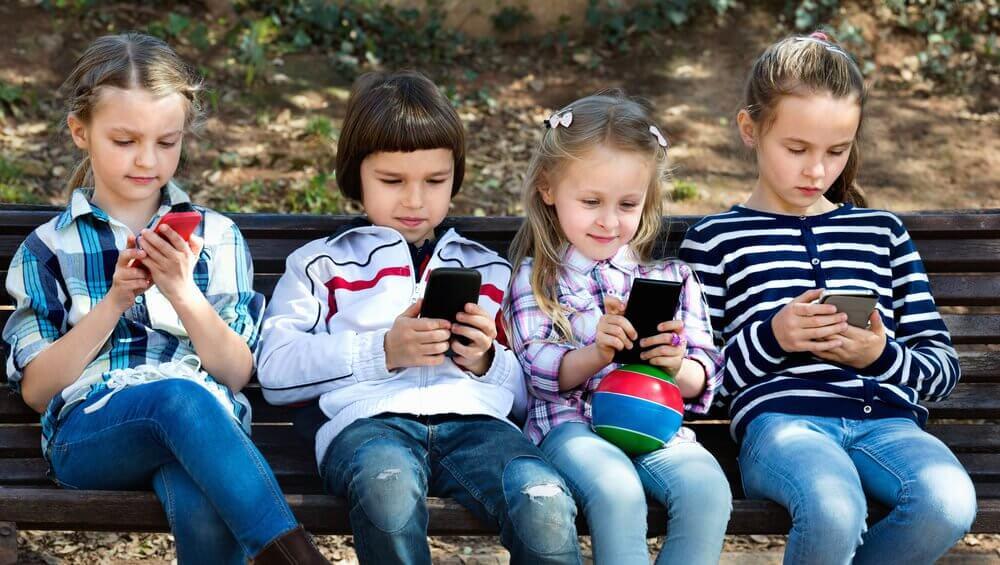 Fire børn på en bænk med deres telefoner