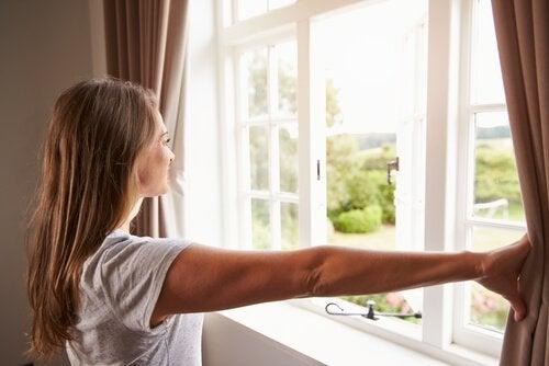 En kvinde kigger ud af vinduet efter at slippe af med lugten af fugt