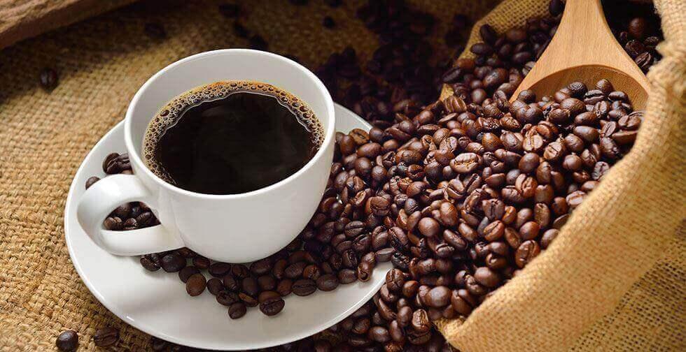 Kaffebønner ved siden af en kop kaffe