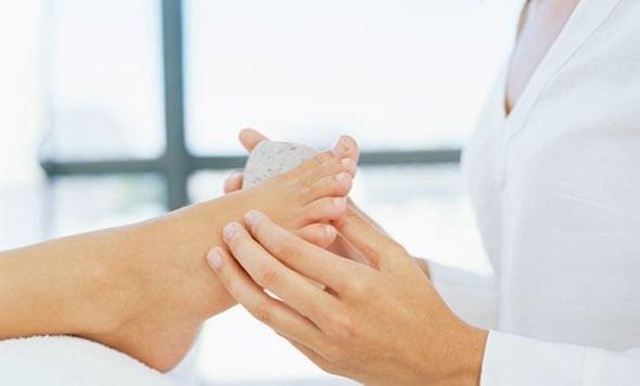 Kvinde fjerner ligtornene på fødderne med en pimpsten