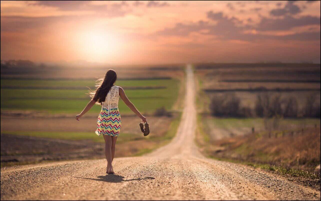 Kvinde med højhælede sko der går ned ad en lang vej