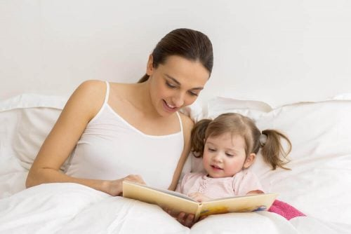Mor der sidder og laeser med sin datter i sengen