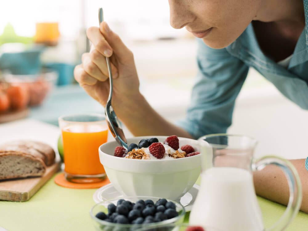 Kvinde spiser en sund morgenmad