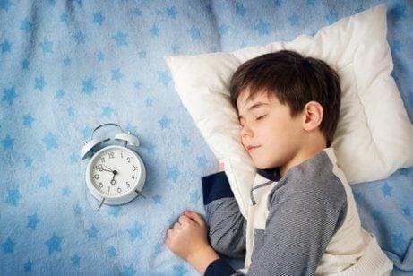 Dreng der sover med et ur ved siden