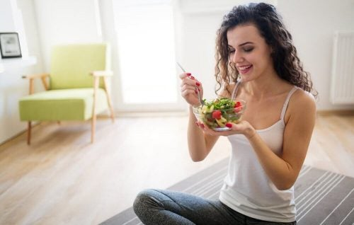 Kvinde spiser salat i stuen