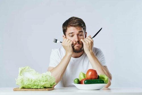 Mand der sidder trist med en salat