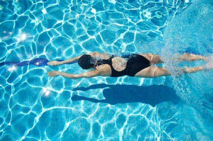 Kvinde svømmer i pool