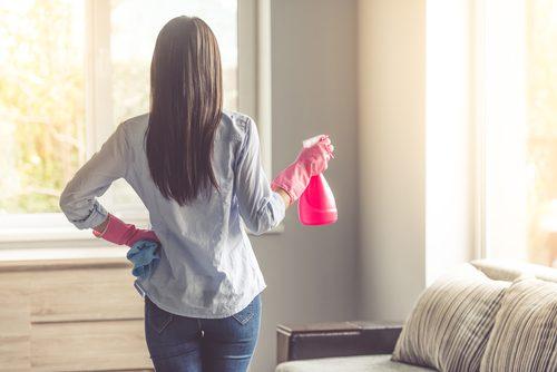 Kvinde gør rent med pink sprayflaske
