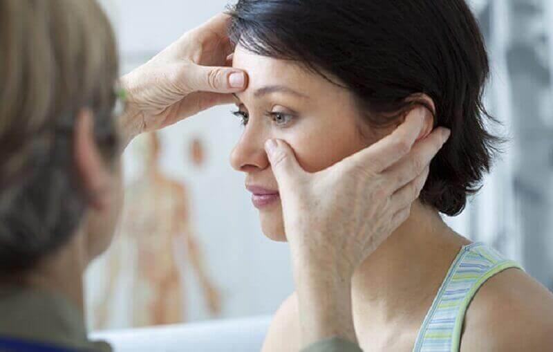 En læge undersøger en kvinde til næsepolypper.