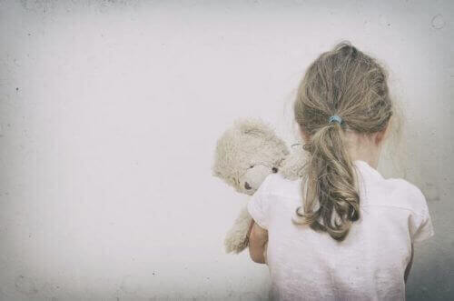 et ensomt barn, der krammer en bamse