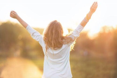 Kvinde som løfter armene i vejret