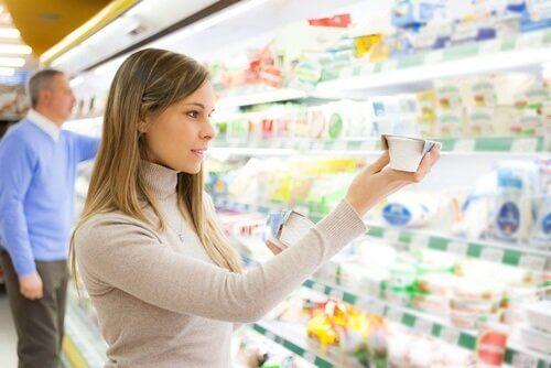 Kvinde kigger på udløbsdatoen på madvarer