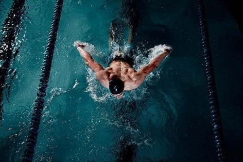 Mand svømmer i svømmehal